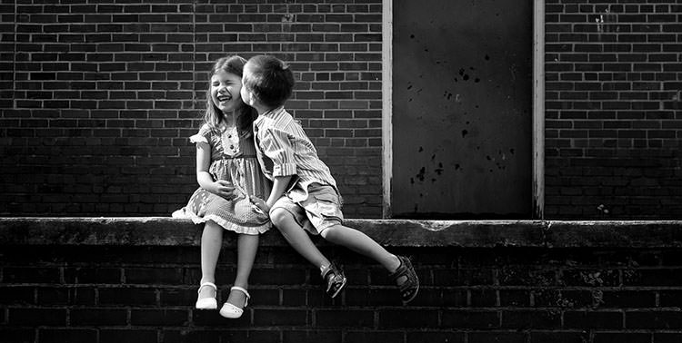 Kids kissing outside.